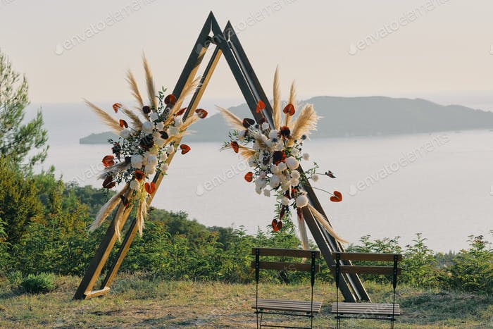Original wedding arch on top of the mountain with white and red flowers at sunset