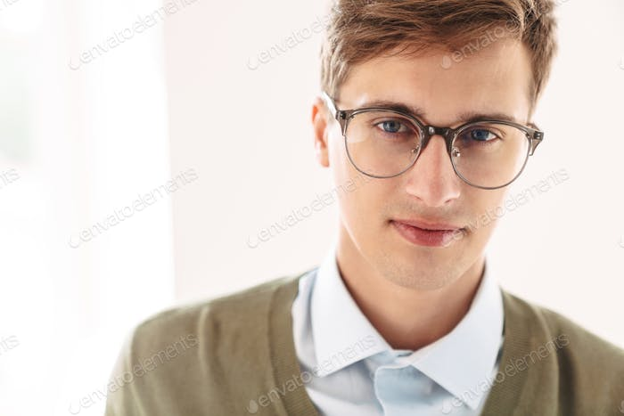 Serious young guy student posing indoor in eyeglasses.