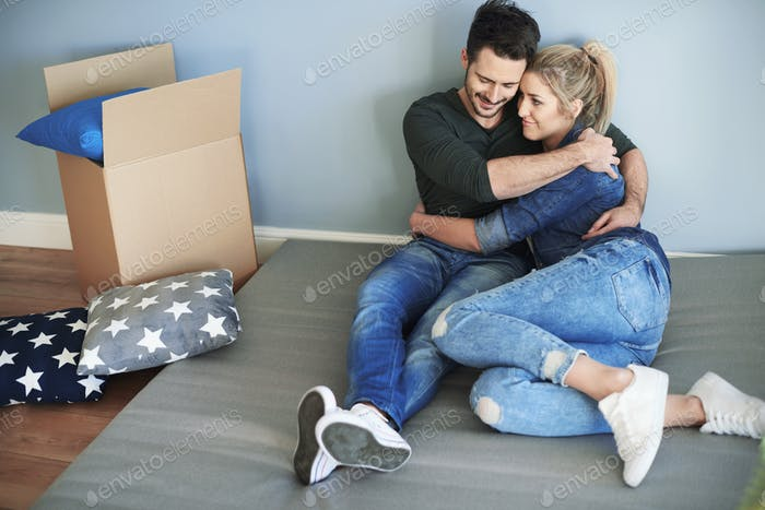 Couple lying down on the floor in their empty house