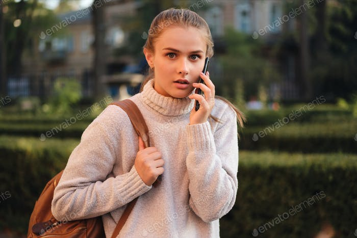 Shocked student girl in sweater talking on cellphone amazedly looking in camera outdoor