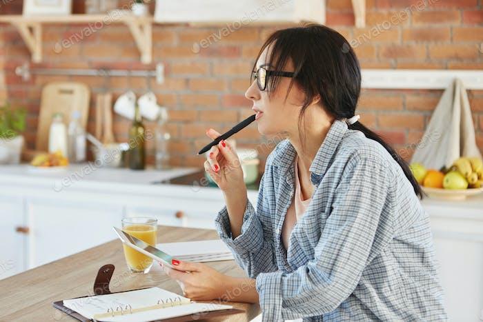 Horizontal portrait of brunette female wears loose casual shirt, looks pensively aside, holds pen an