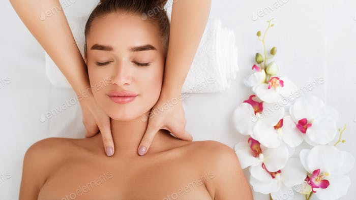 Woman getting neck massage, relaxing with orchid flowers nearby