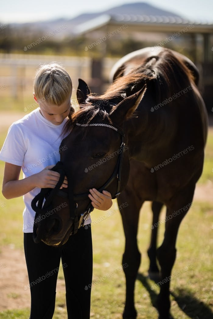Smiling girl caressing the horse in the ranch