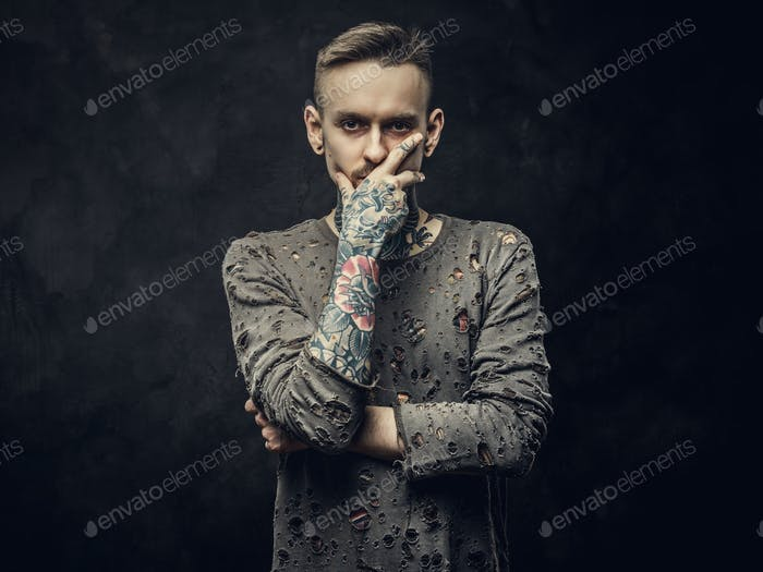Inked young adult male wearing ripped jumper posing in a dark studio on a grey background