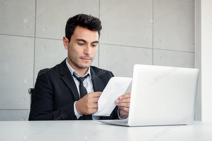 Männliche Mitarbeiter halten Dokumente in Skepsis.