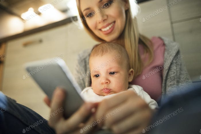 Beautiful mother with son in the arms, holding smartphone