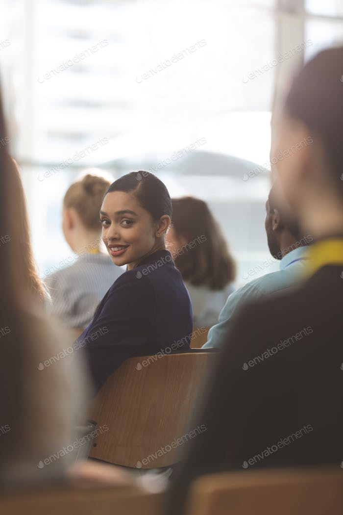 Young businesswoman looking at camera during seminar in office building