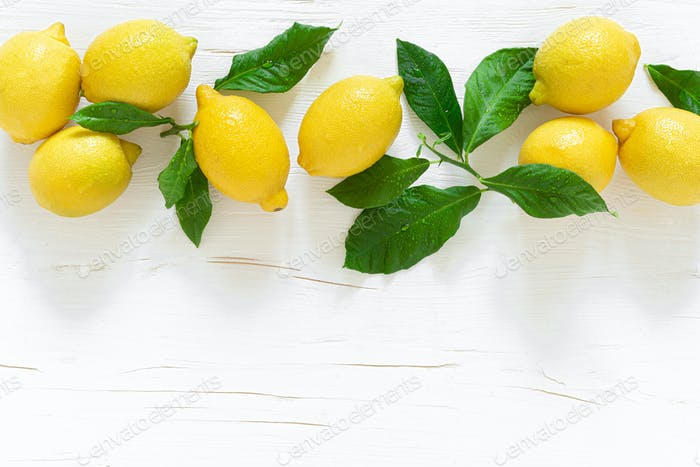 Fresh lemons with leaves on white wooden background,  summer lemonade ingredient