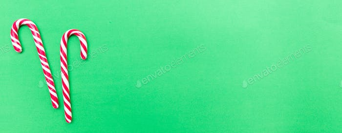 Candy canes on green background, banner, copy space