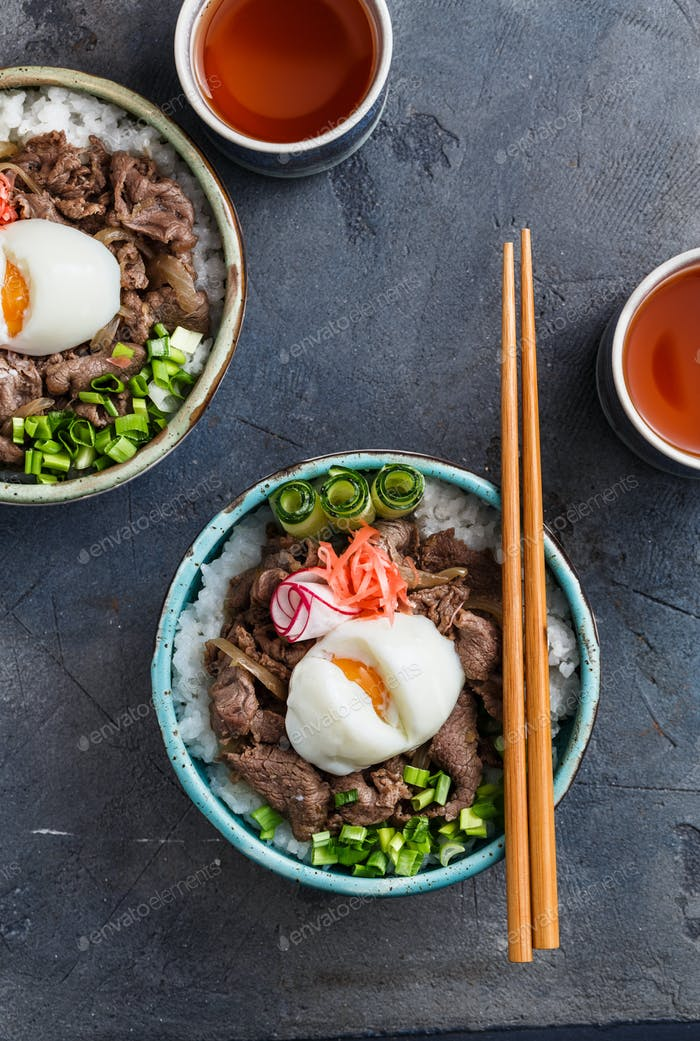 Close view of beef and rice bowl topped with egg and onion