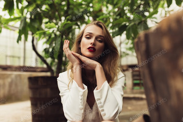 Close up young beautiful woman in white jacket and dress dreamil