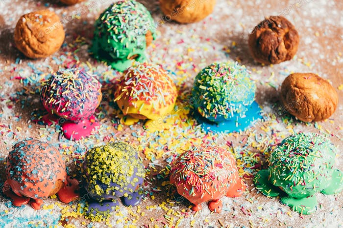 Colorful sprinkled doughnuts on a dirty counter.