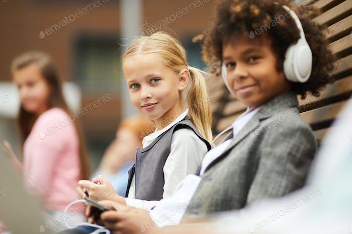 Schulmädchen mit ihrem Klassenkameraden im Freien