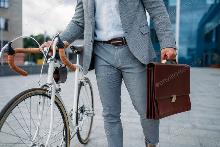 Businessman with briefcase and bicycle in downtown