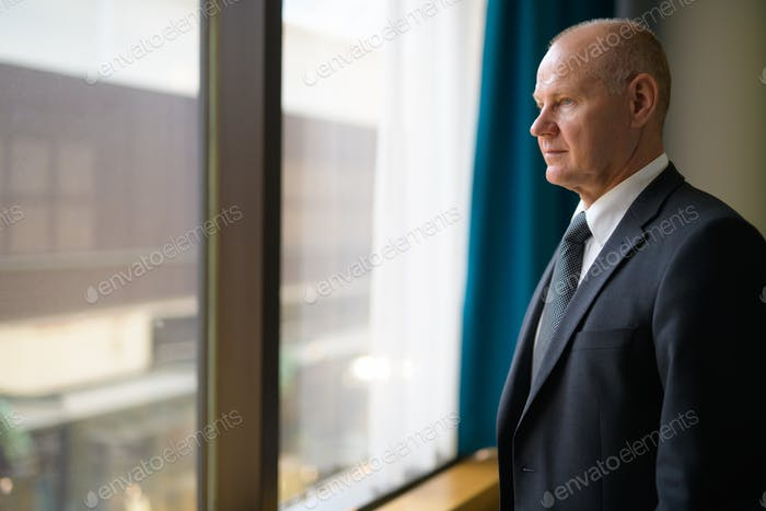 Senior Businessman Thinking While Looking Through The Window And Planning Ahead