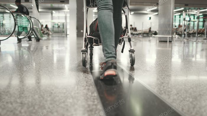 woman carry luggage cart walk at airport terminal
