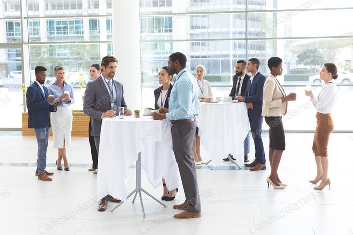 Front of view of diverse business people interacting with each other at table in office lobby