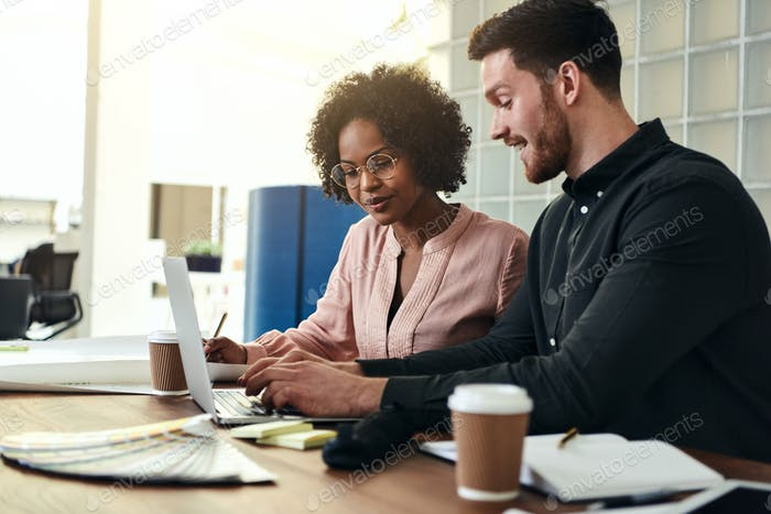 Diverse colleagues using a laptop together at an office desk