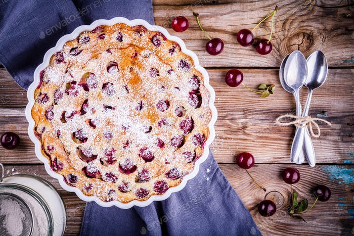 Clafoutis cherry pie on  wooden background