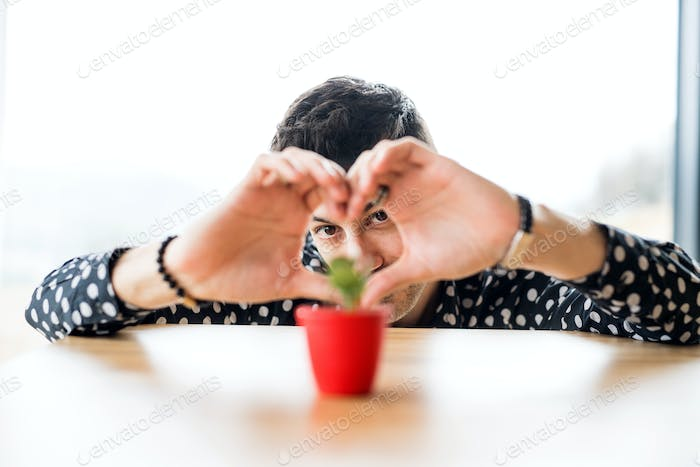 Young man in love with small plant on table indoors at home