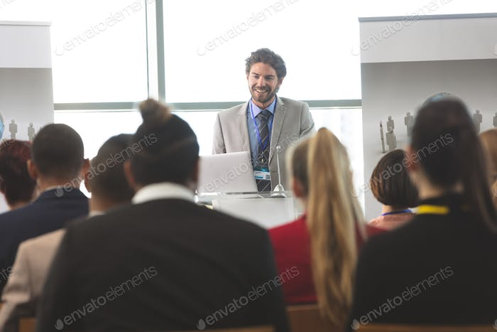 Handsome businessman with laptop speaking in front of business people sitting at seminar in office