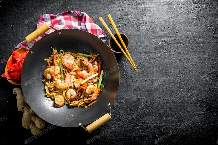 Finished Udon noodles in a wok pan with soy sauce, chopsticks and a napkin.