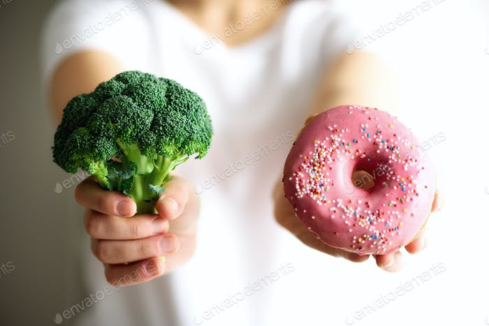 Young woman in white T-shirt choosing between broccoli or junk food, donut. Healthy clean detox