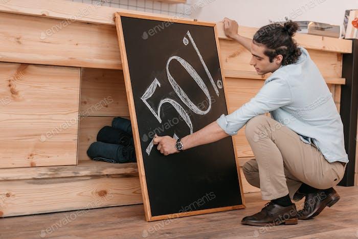 joven vendedor hombre dibujo cincuenta por ciento signo de descuento en la pizarra