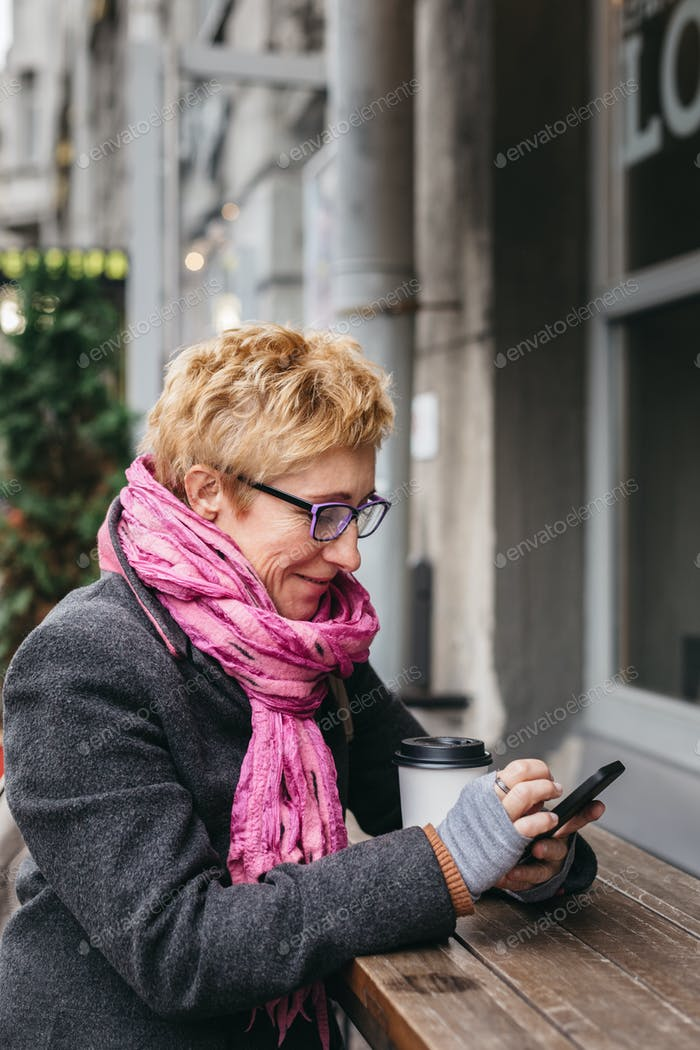 Woman browsing smartphone in outside cafe