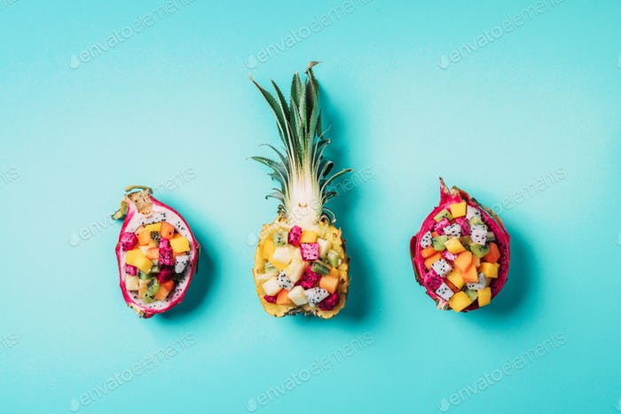 Exotic fruit salad served in half of dragon fruit and pineapple fruit on blue background. Copy space