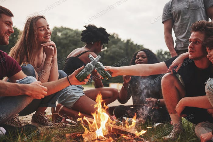 Drunk and happy. Group of people have picnic on the beach. Friends have fun at weekend time