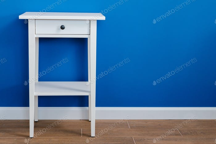 White wooden nightstand table against blue wall