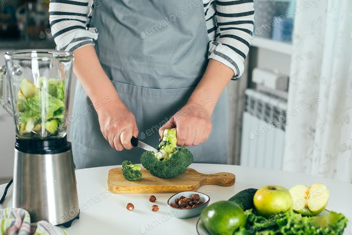Woman cuts broccoli, makes healthy green smoothie. Vegetarian, clean eating lifestyle concept