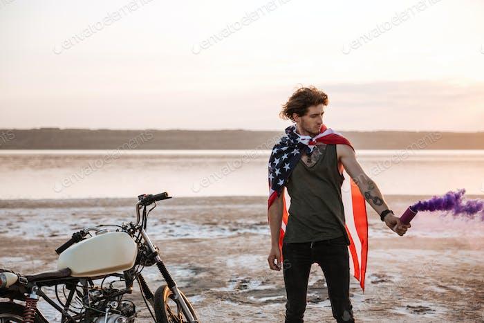 Man wearing american cape holding smoke bomb
