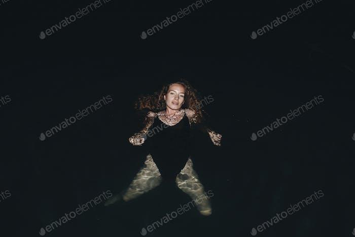 Woman swimming in the dark