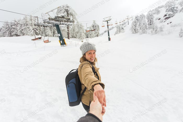 Follow me girl holding boyfriend hand in winter snow nature. Ski resort on the background