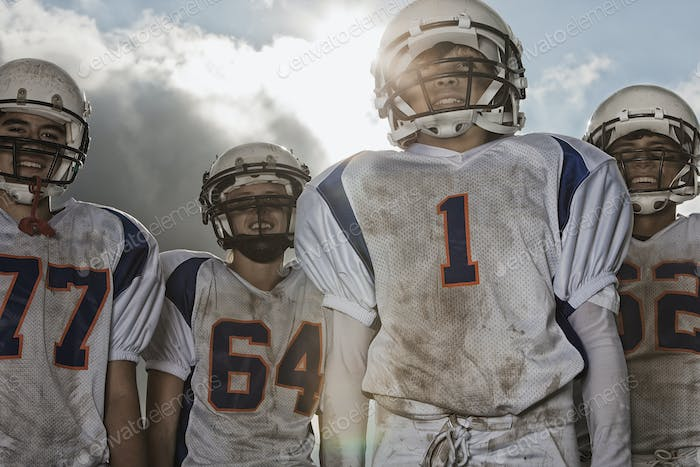 A group of football players, in uniform and helmets