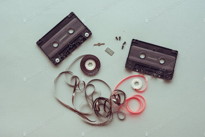 Flat lay audio cassette parts on pastel blue background