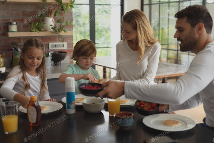 Front view of Caucasian family having food at dining table in a comfortable home