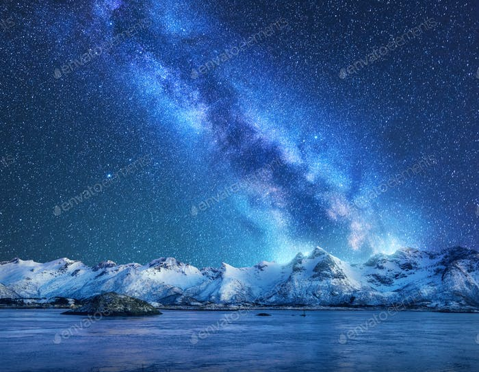 Bright Milky Way over snow covered mountains and sea at night