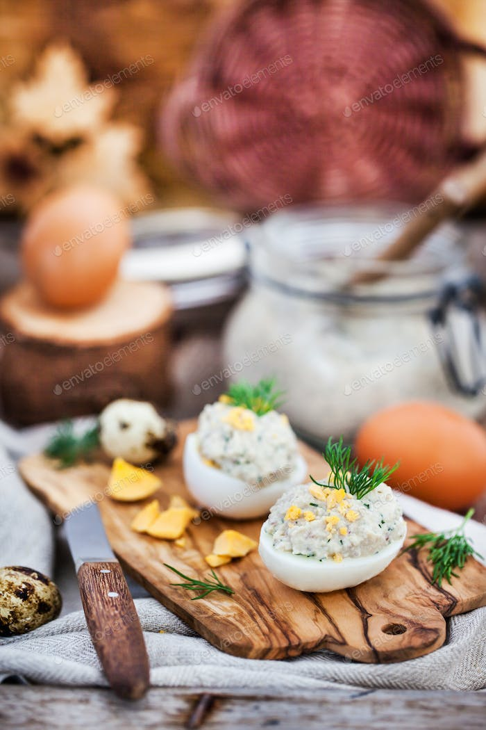 Eggs stuffed with herring creamy pate on wooden rustic backgroun