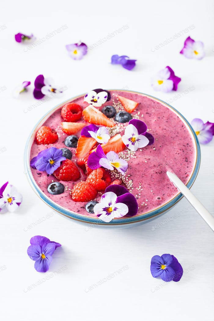 healthy summer berry smoothie bowl with flowers and chia seed