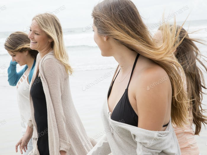 Four young women walking on a beach.