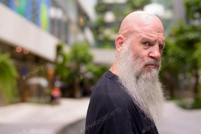 Face of mature bald bearded man looking serious at camera with nature in the city