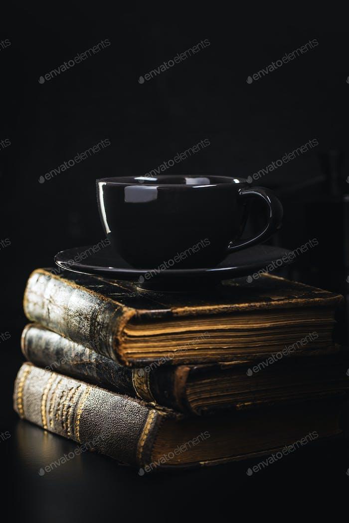 Coffee mug and antique books.