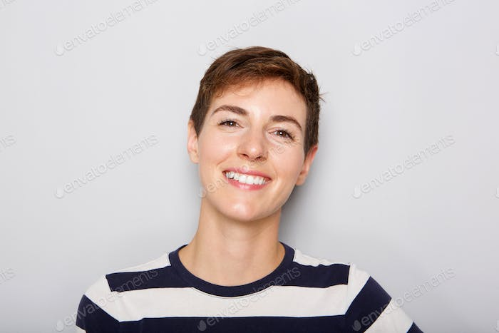 Front portrait of beautiful young woman against gray background