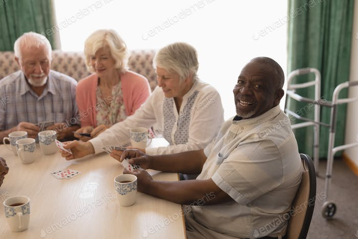 Front view of group of happy senior people playing cards in living room at home