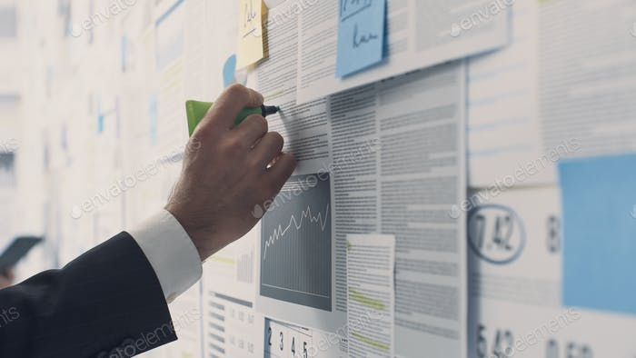 Businessman analyzing financial charts and reports