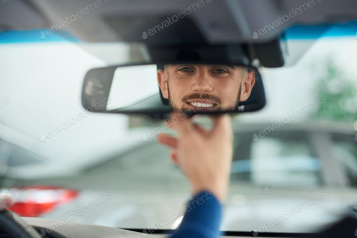 Young man looking in rear view mirror