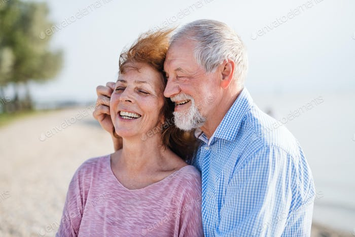 Close-up of senior couple on a holiday on a walk, hugging.